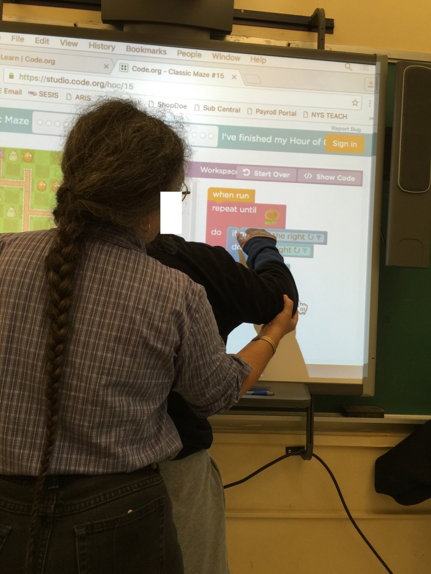 "Jeanne Stork assisting a student during a preview lesson for ""Hour of Code"""