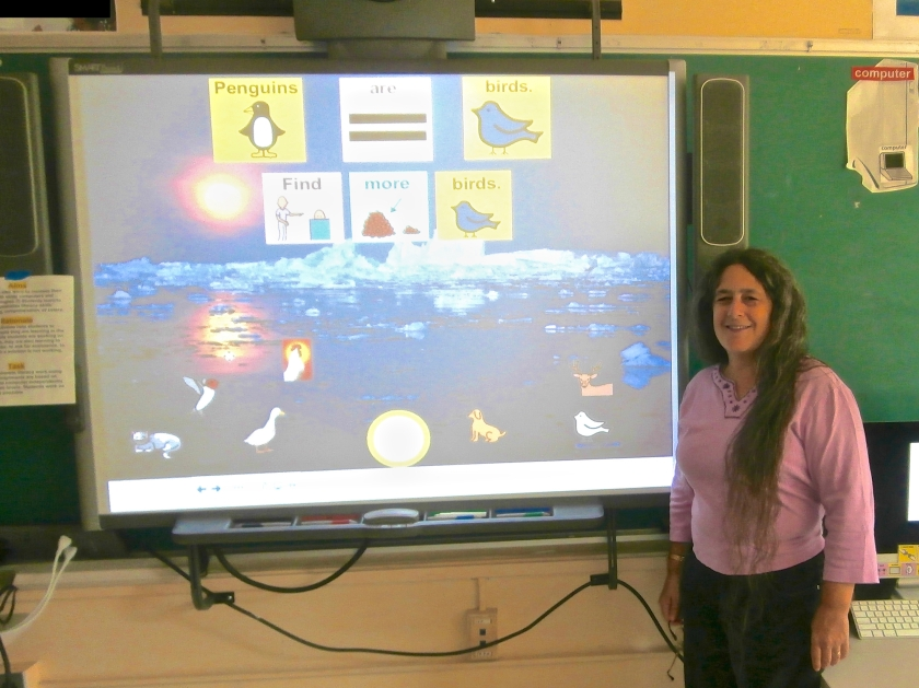 Jeanne Stork standing next to an interactive whiteboard activity that she created