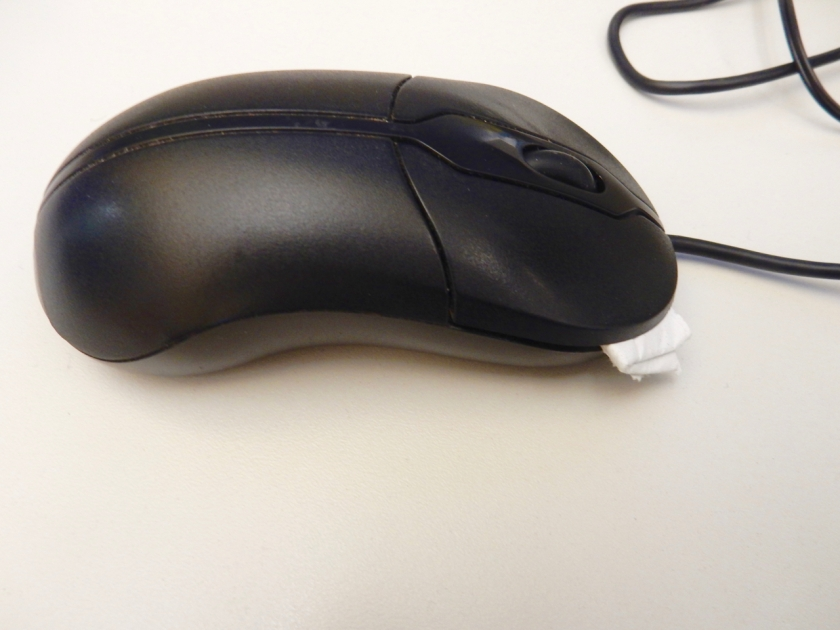 two-button mouse with folder paper towel under one button to disable it