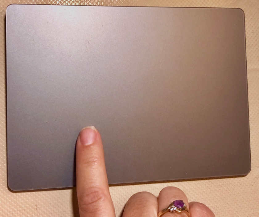 My right index finger is touching a gray Apple Magic Trackpad 2