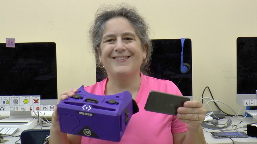 Jeanne Stork is holding Merge V.R. goggles and an iPod Touch or iPhone.